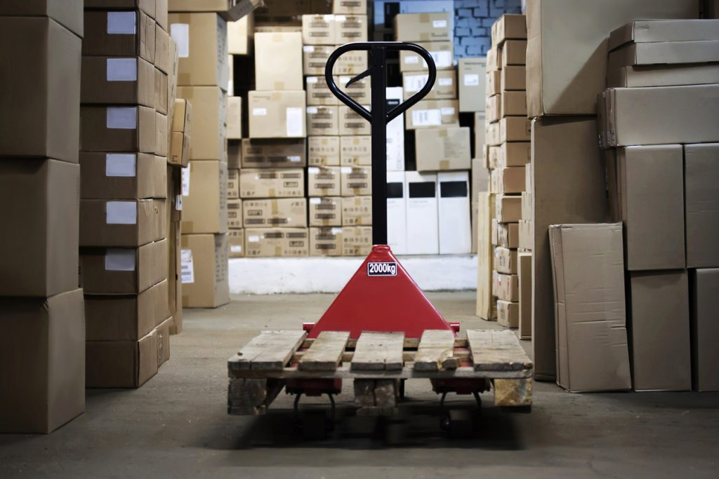 Warehouse with goods in boxes and trolleys for transportation of goods close-up
