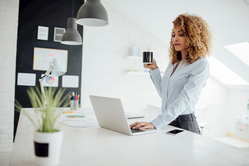 woman at standing desk drinking coffee