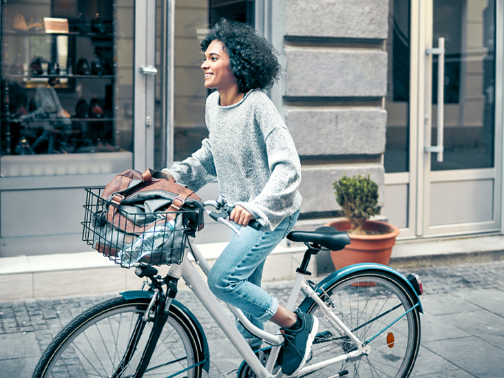 Woman-Riding-Rented-Bicycle-In-A-City.-Cycling-and-smiling-