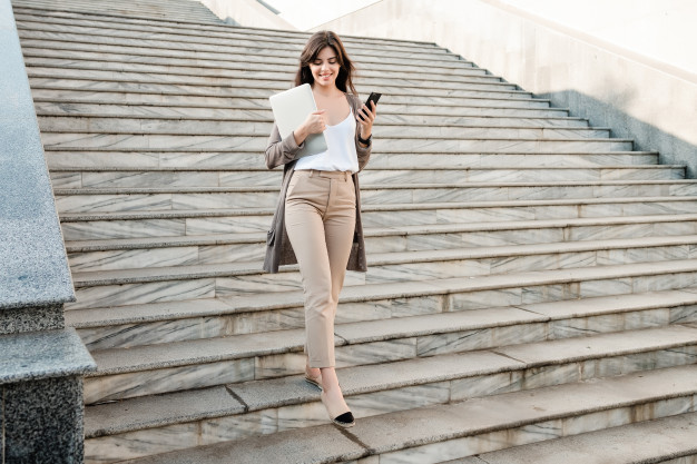 beautiful-woman-walking-down-stairs-with-laptop-phone