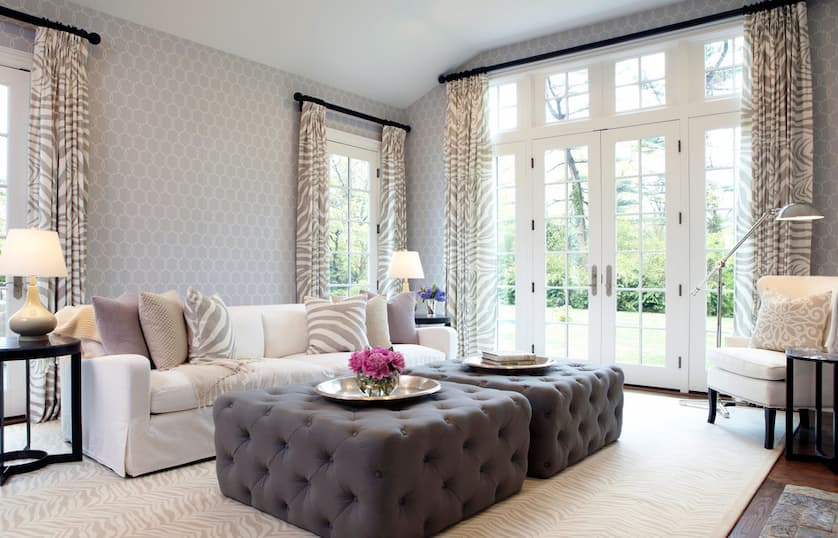 living room with beige sofa bed and gray ottomans as a tables