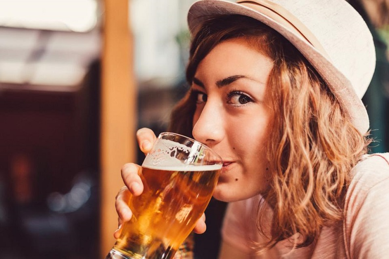 girl taking a sip from a glass of beer
