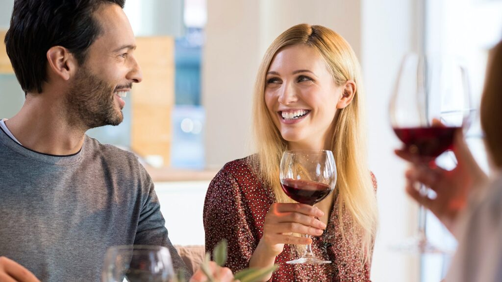 couple smiling while drinking wine
