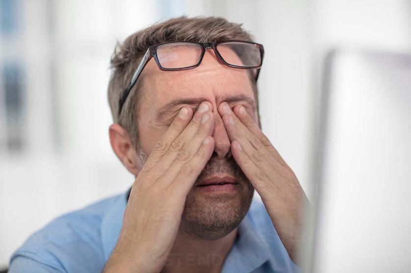 stressed-man-rubbing-eyes-image