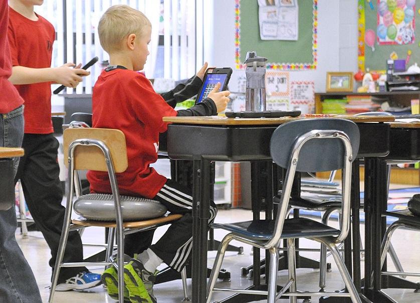 kid seating on cushion in classroom